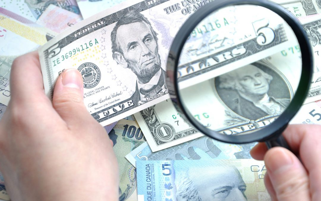 Image of Inspecting Cash with a Magnifying Glass Representing Countermeasure to Counterfeit Currency