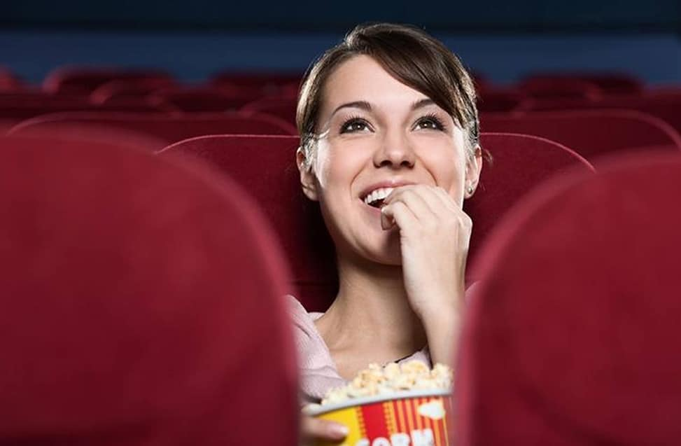 Woman watching movie, representing theater cash transactions secured by Tidel Cash Recyclers.